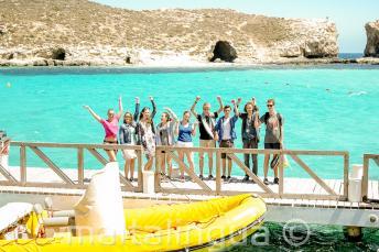 Группа студентов машет напротив лодки в Голубую Лагуну, Комино