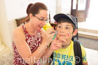 Сотрудник наносит аппликацию на лицо ребенка