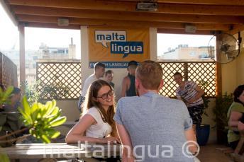 Студент курса английского разговаривает с преподавателем на террасе