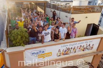 Студенты курсов английского языка машут на верхней терассе школы