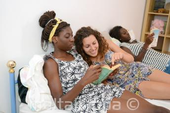 Студент читает книгу вместе с членом принимающей семьи