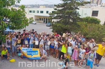 Большя группа юных студентов машет возле летней школы