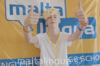 Летний студент школы показывает пальцы вверх