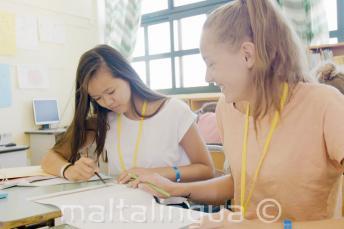 2 девочки работают вместе над английским заданием на уроке