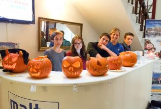 Юные студенты с резными тыквами на Хэллоуин за ресепшеном школы