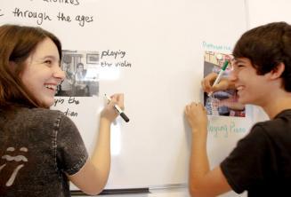 2 студента работают вместе на доске в классе