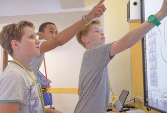 Преподаватель помогает 2 студентам работать на интерактивной доске