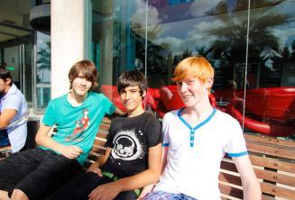 3 студента сидят на скамейке снаружи школьной резиденции