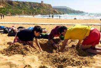 Групп-лидер и дети копают ямку на пляже