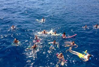 Большая группа студентов языковой школы плавают вместе