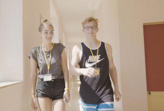 Подростки мальчик и девочка идут по языковой школе