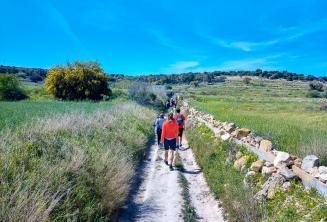 Группа студентов английского идет по сельской местности на Мальте