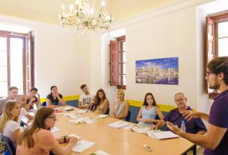Стденты слушают преподавателя в классе на уроке английского языка